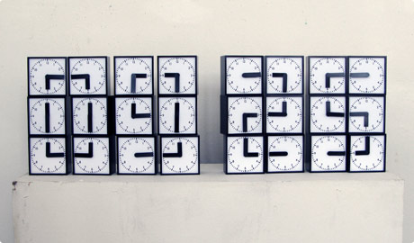 digital clock display made out of rotating analogue clocks